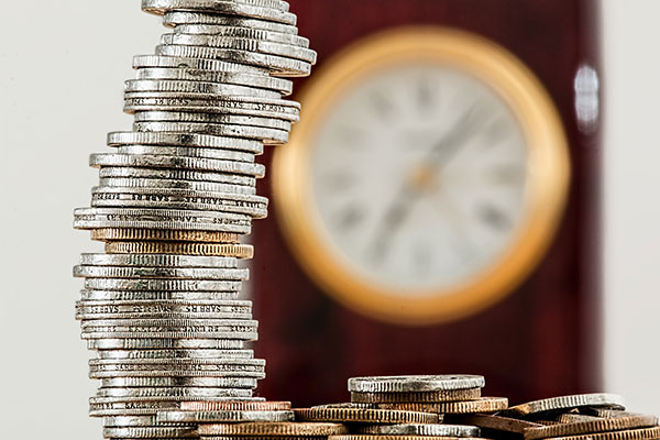 Stack of coins with clock ticking for financial statement preparation deadline