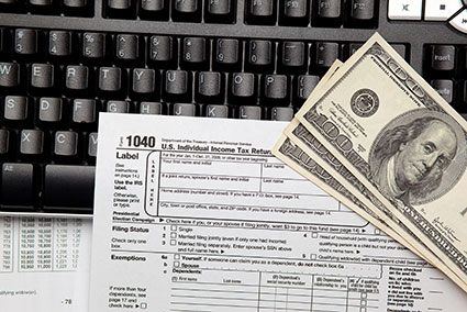keyboard with Federal 1040 tax form and $100 bills